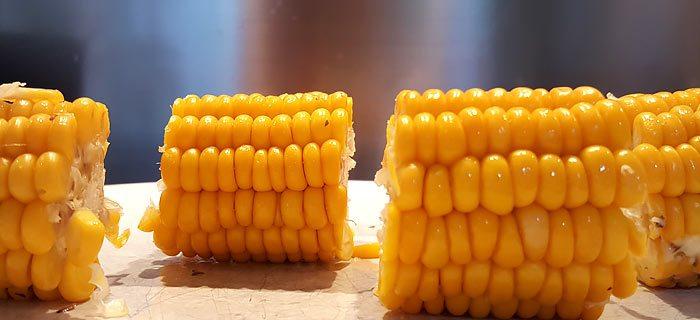 Maiskolven uit de oven met roomboter, oregano en gesmolten kaas