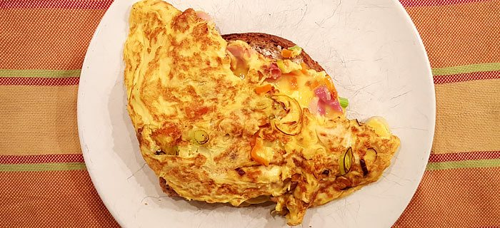 Een stevige omelet met spek, prei, paprika en kaas