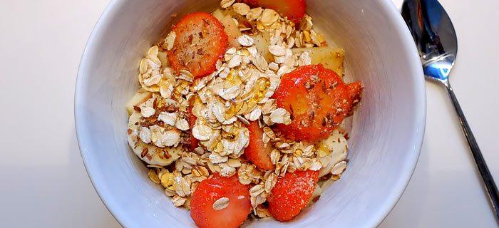 Gezond yoghurtontbijtje met aardbei, banaan, appel en honing