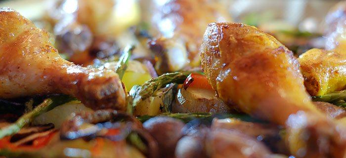 Traybake met aardappel, groene asperges, puntpaprika en drumsticks