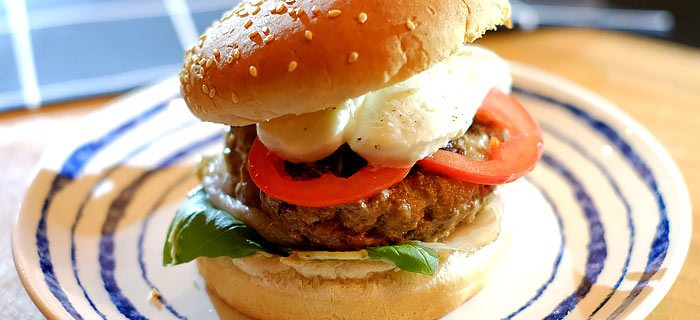 Broodje hamburger met pancetta, tomaat, mozzarella en pestomayonaise