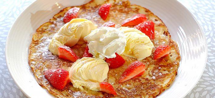 Zomerse pannenkoeken met aardbeien, vanille roomijs en slagroom