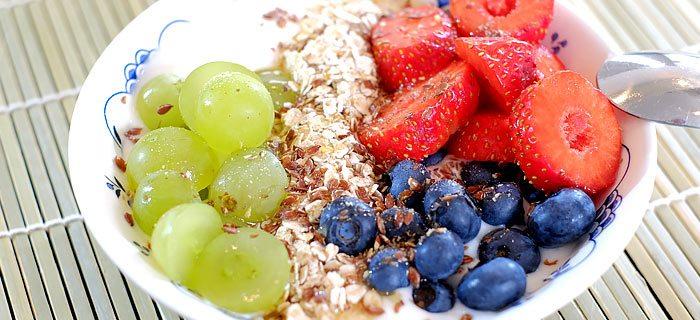 Yoghurt ontbijtje met aardbeien, blauwe bessen en druiven