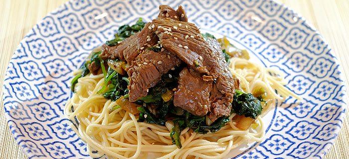 Roergebakken spinazie met noedels en zoete plakjes biefstuk