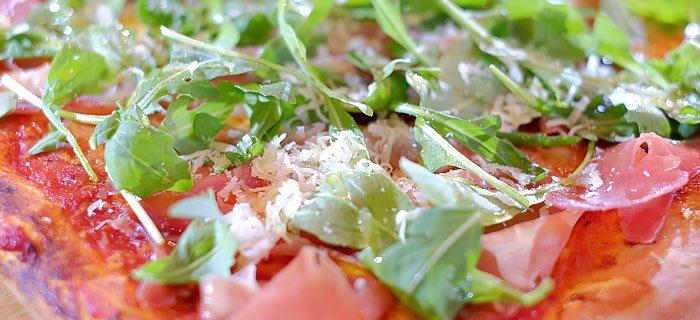 Pizza met parmaham, mozzarella, Grana Padano en rucola