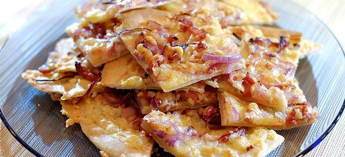 Flammkuchen met rode ui, gebakken spekjes en kaas
