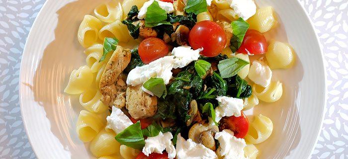 Pasta met spinazie, champignons, tomaatjes, kip pesto en mozzarella