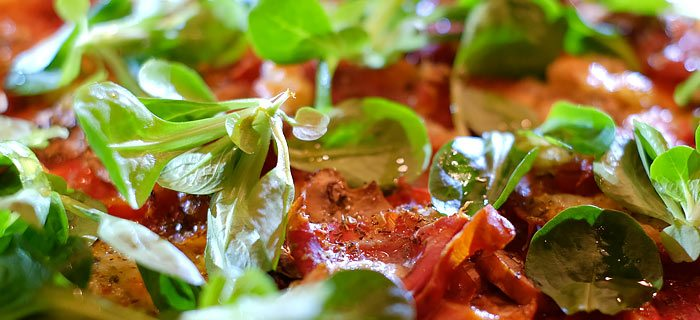 Pizza met parmaham, champignons, mozzarella, truffelolie en veldsla