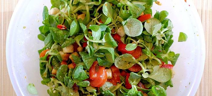 Salade van veldsla met tomaat, rode paprika en pestodressing