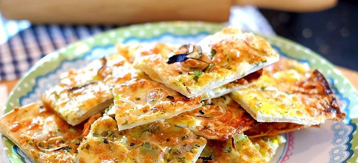 Flammkuchen met ei, sjalotjes, kruiden en kaas