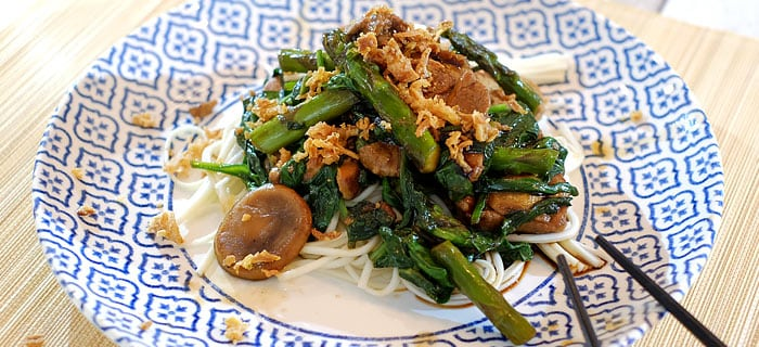 Gemarineerde varkenshaas met groene asperges, shiitake, spinazie en noedels