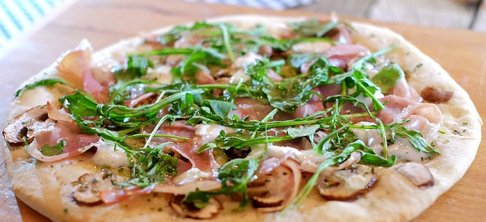 Pizza bianca met prosciutto crudo, champignons, mozzarella en rucola