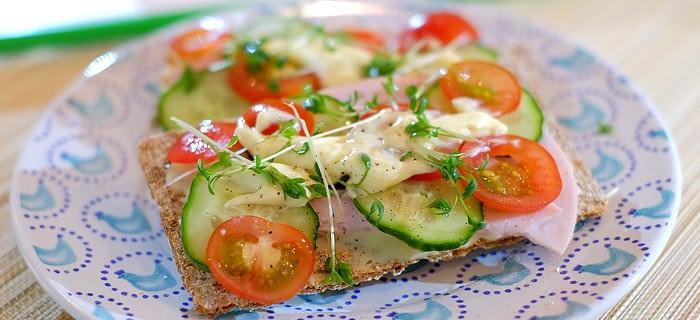 Knäckebröd met smeerkaas, kalkoenfilet, komkommer, tomaat en tuinkers