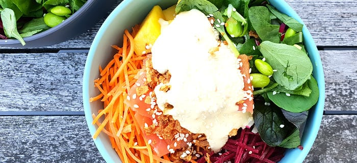Poké bowl met rode biet, wortel, mango, sojabonen, zalm en wasabi-mayonaise
