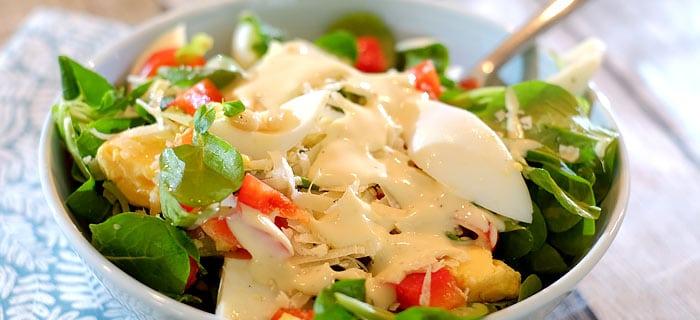 Veldsla met tomaatjes, rode paprika, Parmezaan en een frisse yoghurt-mayodressing