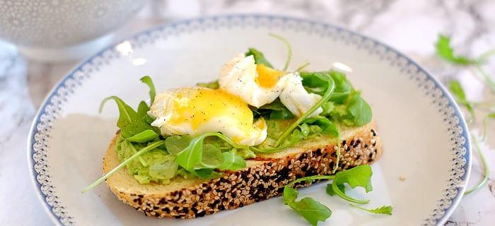 Toast met avocado, rucola en een gepocheerd ei