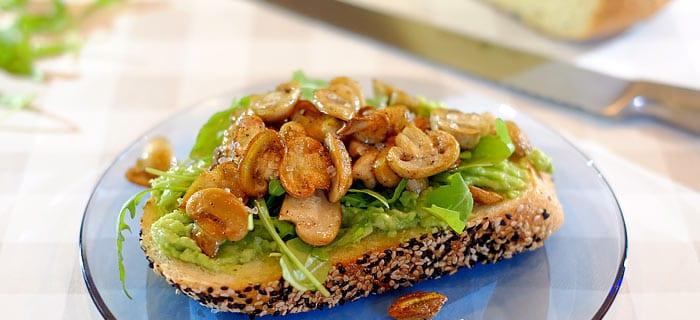 Toast met avocadospread, gebakken champignons en rucola