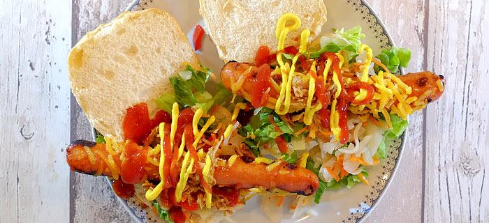 Broodje BBQ hotdog met zoetzure rauwkost, cheddar en gebakken uitjes