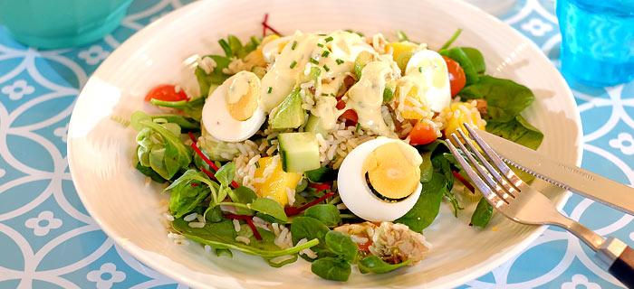 Rijstsalade met mango, avocado, komkommer, tomaatjes, makreel en ei