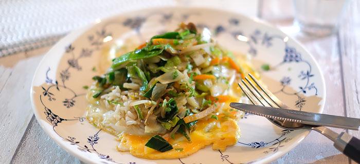 Gebakken ei met rijst en in oestersaus gebakken groenten en champignons