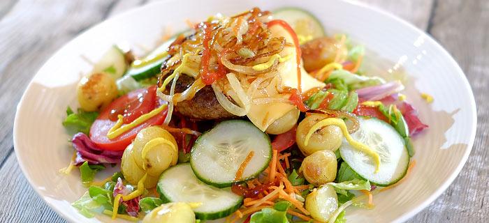Hamburger salade met ovenkrieltjes, uienringen, komkommer en tomaat