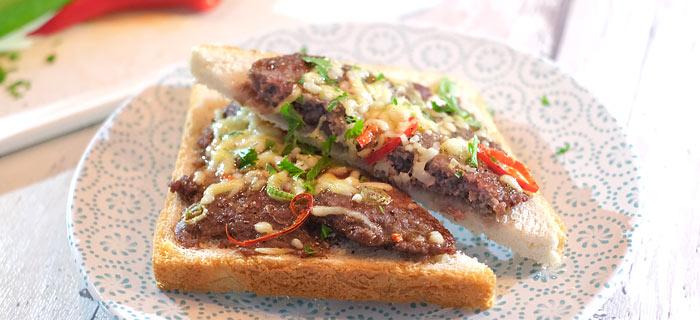 Pikante toast met gegrilde tartaar, lenteui, rode peper en gesmolten kaas