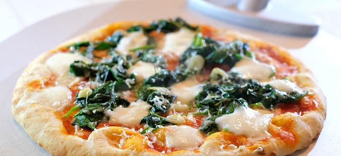 Pizza met spinazie, knoflook, mozzarella en Parmezaanse kaas
