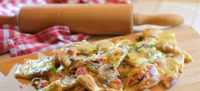 Flammkuchen met zure room, ontbijtspek, champignons en Gruyère