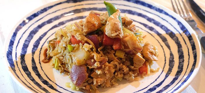Rijst met geroerbakte groenten, stukjes kip en een snelle pindasaus